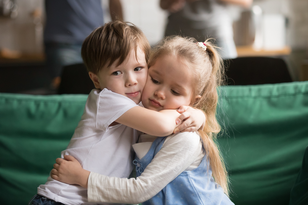 Little brother hugging upset sister sitting together on couch at home, sincere toddler boy embracing depressed girl, apologizing, supporting, good relationship, friendship, compassion, empathy concept